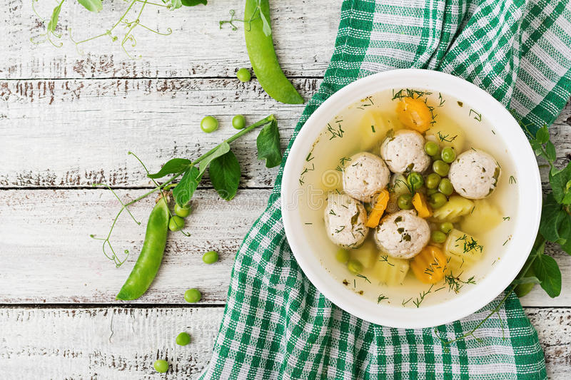 Dietary soup with chicken meatballs and green peas in a white bowl on a wooden background. stock photos