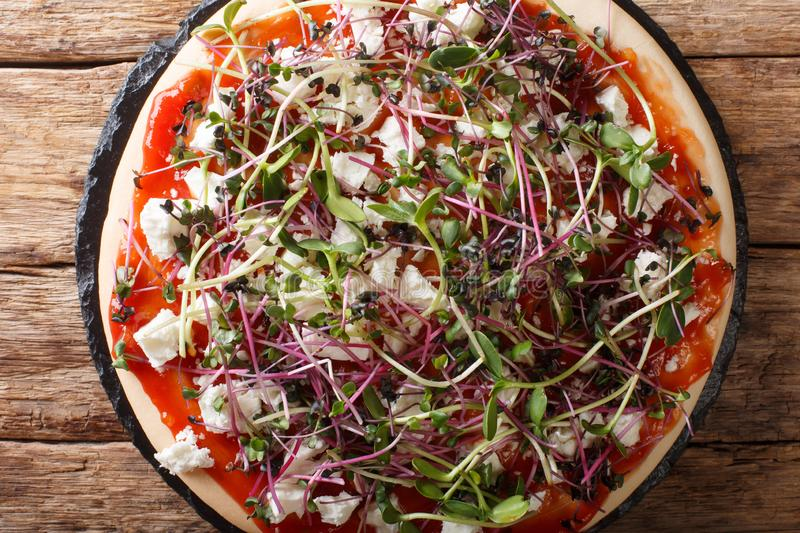 Dietary vegetarian pizza with feta and fresh mix micro green close-up. horizontal top view royalty free stock photography