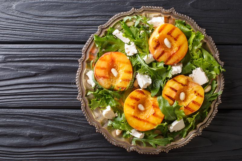 Dietary vegetarian salad with grilled peaches, with feta cheese, arugula, peanuts and herbs close-up on a plate. horizontal top v royalty free stock images