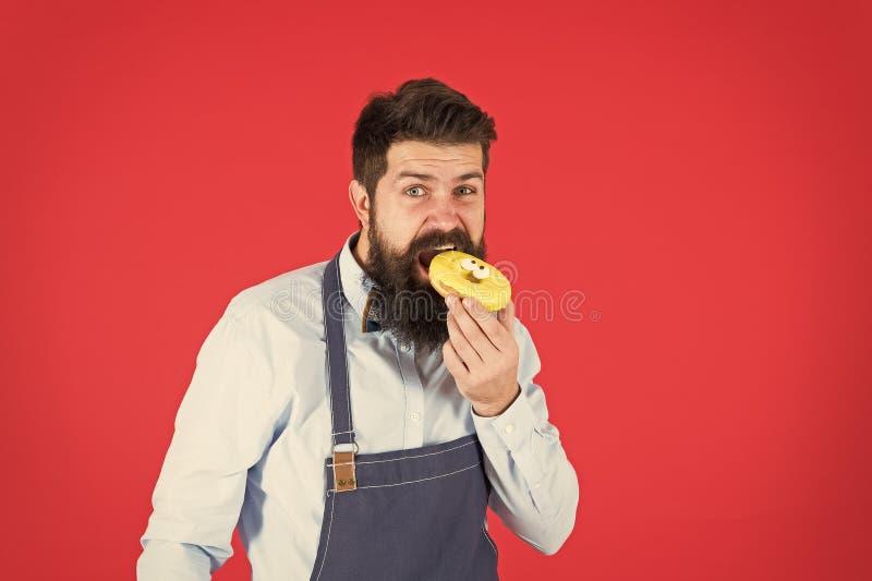 Dieter och hälsosamma livsmedel Ohälsosam kosthållning Baker, ät ringnöt Chef man i kafé Calorie Känn hunger Bearded baker royaltyfria bilder
