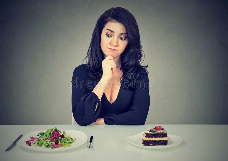 Dieting концепция, женщина выбирая между здоровой едой и вкусным тортом стоковое фото