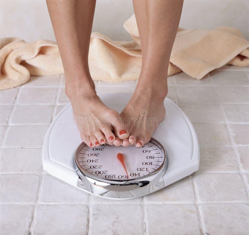 Dieting ноги ` s женщины покрывая чтение масштаба стоковое изображение