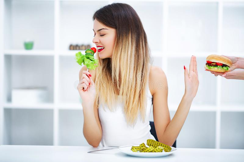 Dieting concept, beautiful young woman choosing between healthy stock photography