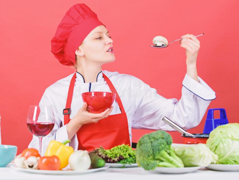 Dieting concept. Eat healthy. Healthy ration. Girl wear hat and apron try mushroom taste. Woman professional chef hold stock photos