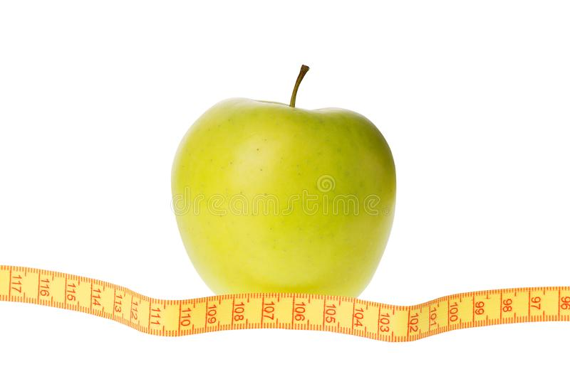 Dieting concept. Green yellow apple with measuring tape isolated on white background stock photo