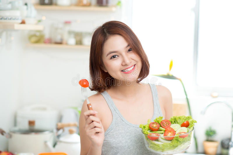 Dieting concept. Healthy Food. Beautiful Young Asian Woman eating fresh vegetable salad. Loosing Weight concept royalty free stock photos