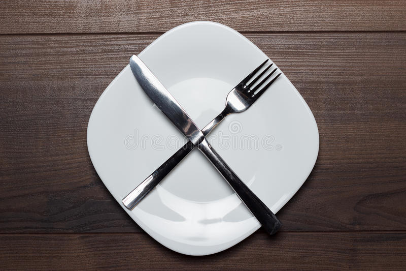 Dieting concept white plate with knife and fork royalty free stock photo