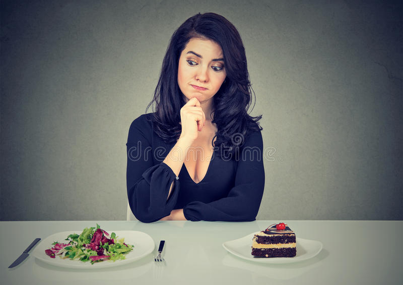 Dieting concept, woman choosing between healthy food and tasty cake stock photo