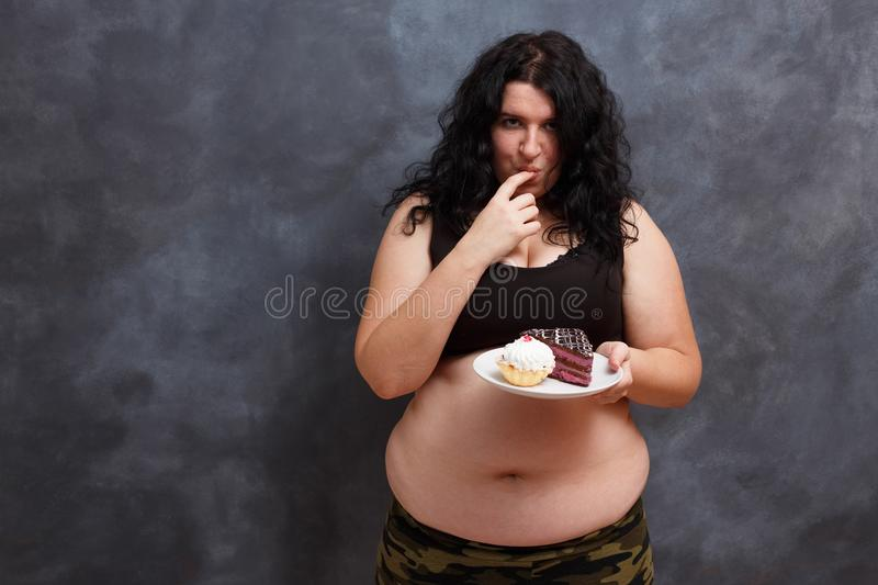 Dieting concept. Young obese overweight woman fighting the tempt royalty free stock photo