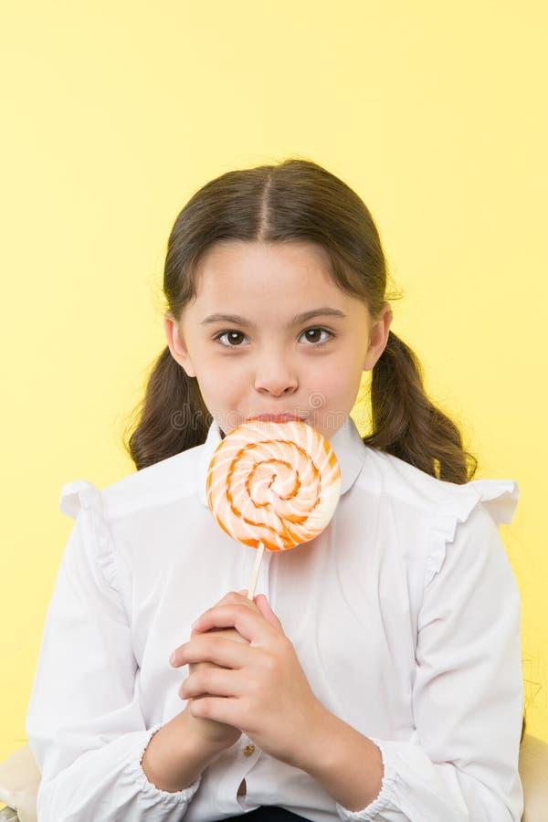dieting dieta e conceito saudável do alimento dieta após comer da sobremesa a menina pequena com ` t do doesn do pirulito gosta d imagem de stock