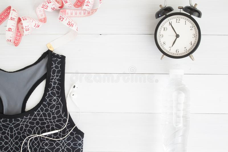 Dieting and fitness concept with sport bra, measuring-tape, water and alarm clock on vintage white wooden background, Flat lay royalty free stock photos