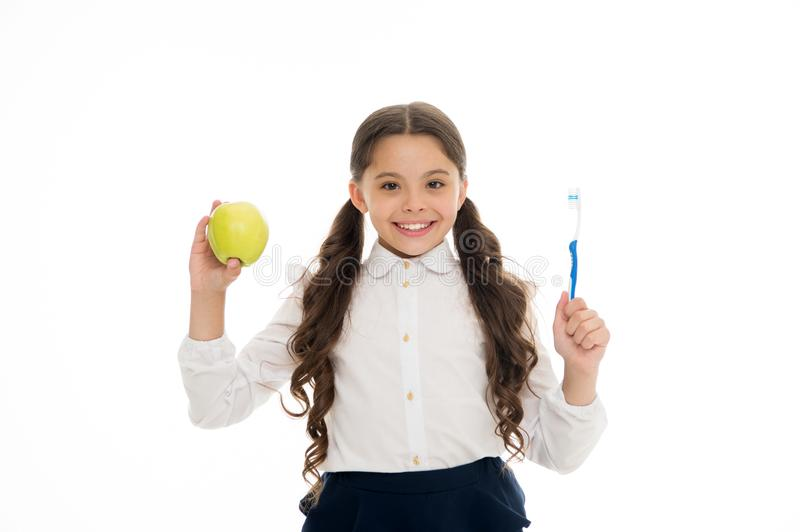 Dieting and health. Development of children. Little child smiling with tooth brush and green apple. Happy girl isolated royalty free stock photo