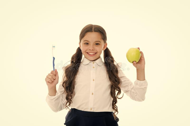 Dieting and health. Development of children. Little child smiling with tooth brush and green apple. Happy girl isolated. On white. Teeth care and whitening royalty free stock photos
