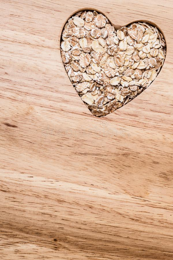Oat cereal heart shaped on wooden surface. Dieting healthcare concept. Oat cereal oatmeal heart shaped on wooden surface. Healthy food for lowering cholesterol royalty free stock photos