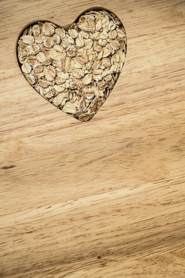 Oat cereal heart shaped on wooden surface. Dieting healthcare concept. Oat cereal oatmeal heart shaped on wooden surface. Healthy food for lowering cholesterol stock images