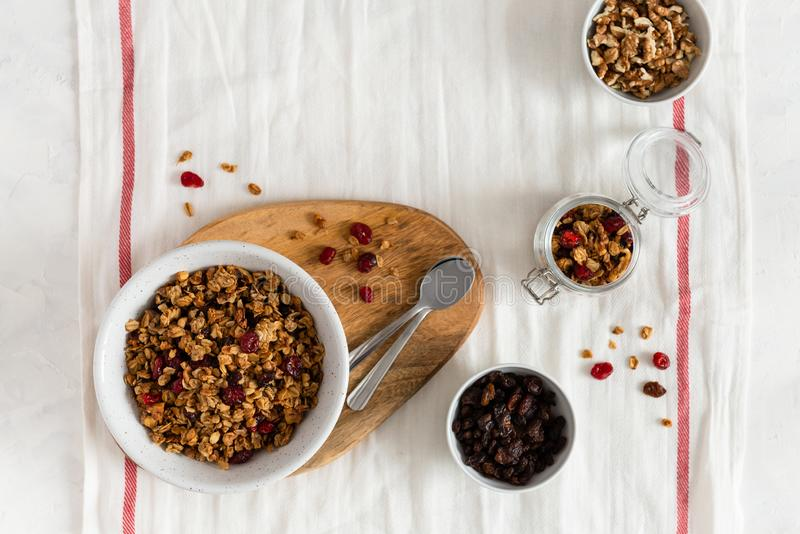 Dieting. Healthy food. Bowl of homemade granola with nuts and fruits on white linen background. Top view, copy space stock image