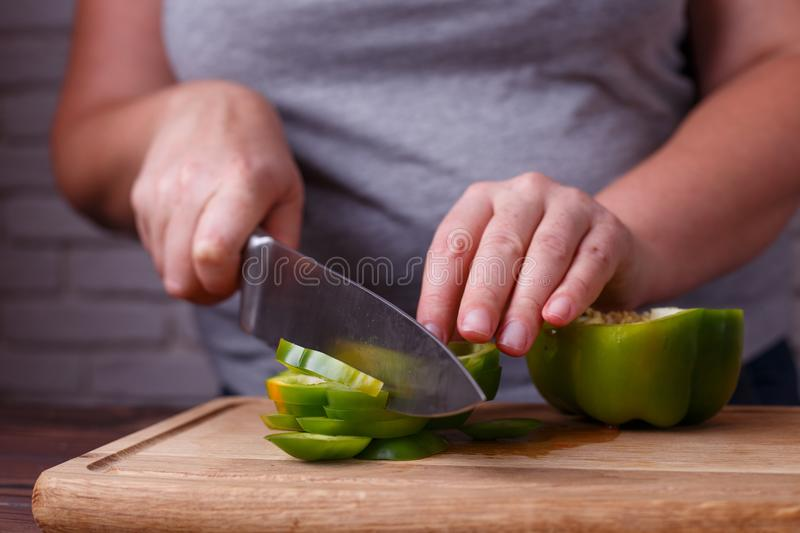 Dieting, healthy food, low carb diet. Hands slicing bell pepper, royalty free stock photography