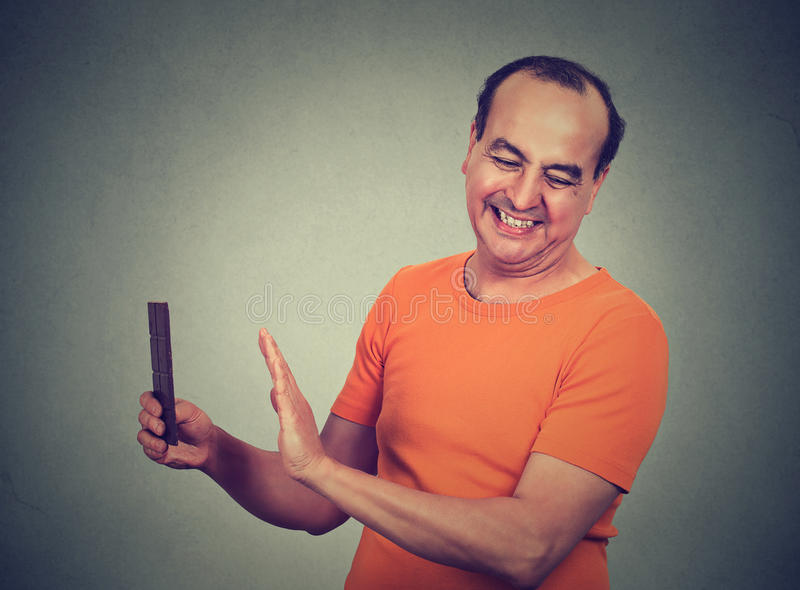 Dieting man. Confused man trying to withstand, resist temptation to eat chocolate. Dieting man. Closeup portrait confused, funny looking middle aged man trying royalty free stock images