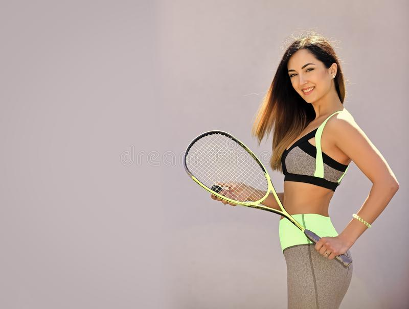 Dieting and sport game, copy space. Woman in sportswear with squash racket on grey background. Girl athlete with sport bat with happy face. Sport and success stock photography