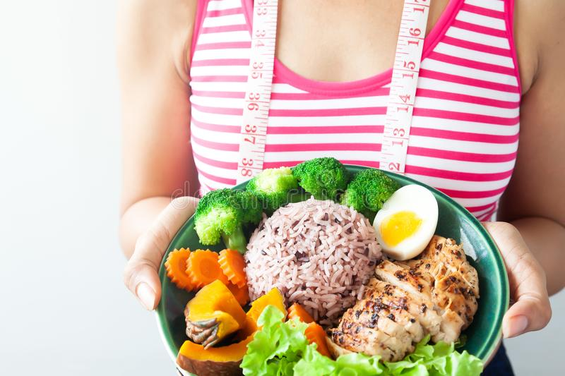 Dieting woman with healthy food. Rice berry with grilled chicken. Breast and vegetables stock photo
