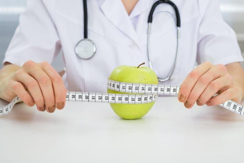 Dietist som mäter det gröna äpplet fotografering för bildbyråer