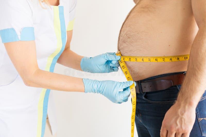 Dietist som m?ter mans feta m?tningar f?r mage under unders?kning arkivfoton