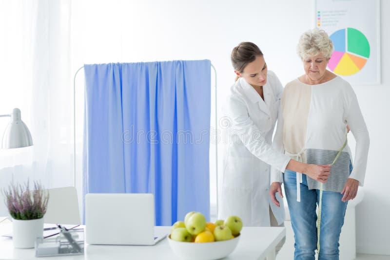 Dietist som mäter strömkretsen för kropp för kvinna` s royaltyfria foton