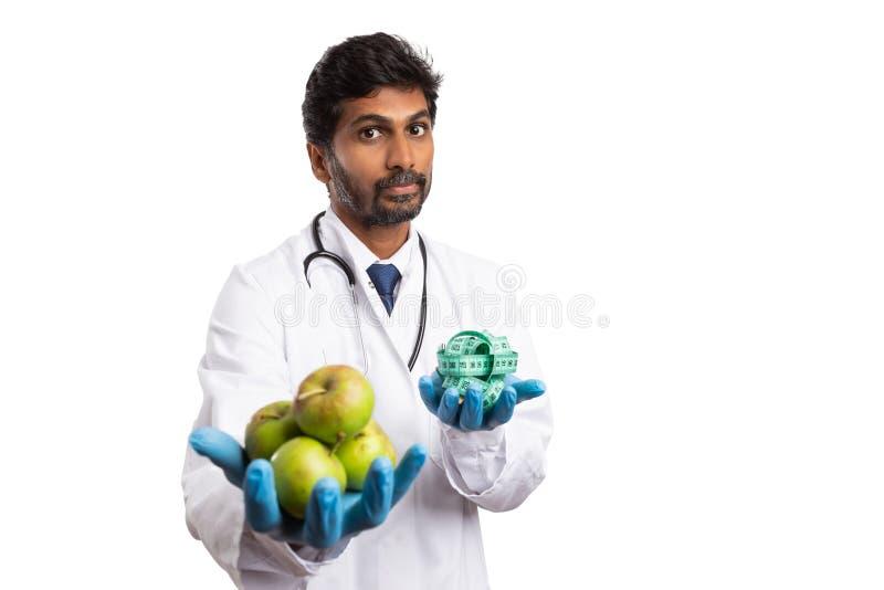 Dietist som rymmer äpplen och mäter bandet royaltyfri foto