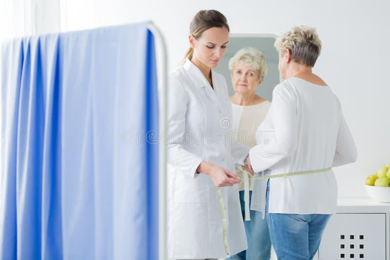 Dietista que mede o circuito paciente do corpo do ` s imagem de stock