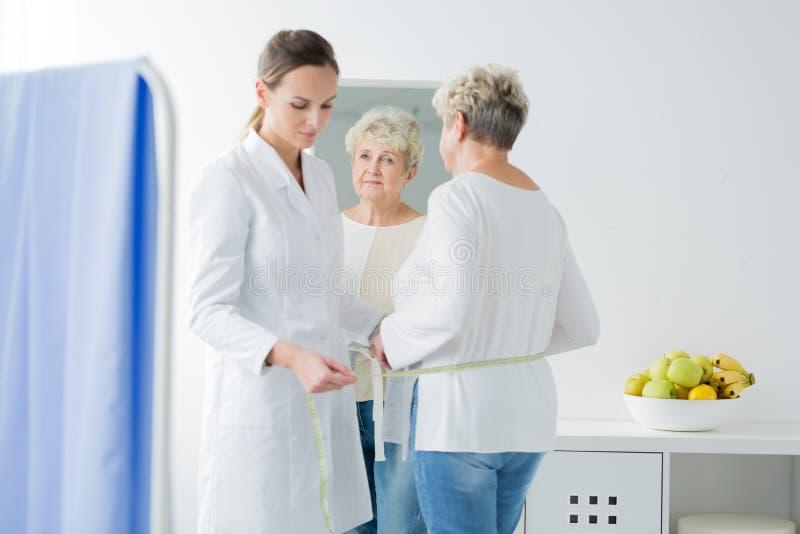 Dietista que toma medidas do paciente imagem de stock