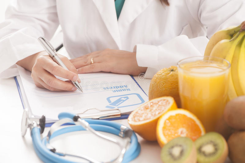 Dietitian doctor. With prescription and fruits stock photography