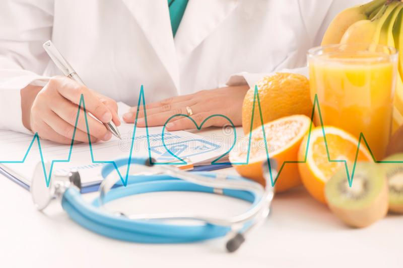A dietitian doctor. Dietitian doctor writing a diet list with fruit on a desk stock photo