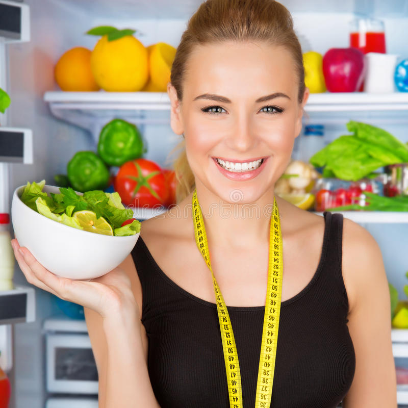 Dietitian with fresh salad. Closeup portrait of beautiful cheerful girl holding in hand bowl with fresh tasty green salad, dietitian recommending eating royalty free stock photography