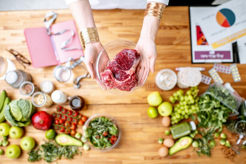 Dietitian holding meat above the table full of healthy food royalty free stock image