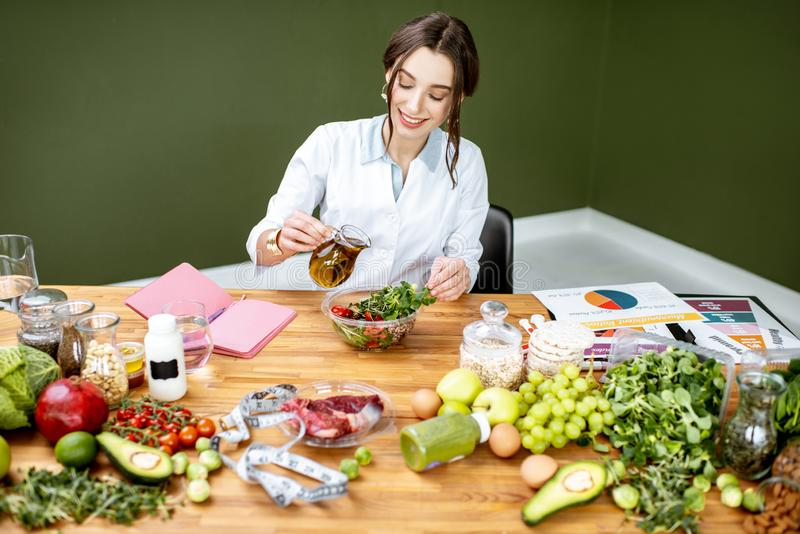Dietitian making a salad. Woman dietitian working on a healthy diet pouring olive oil into the salad sitting at the table full of various healthy food indoors stock photos
