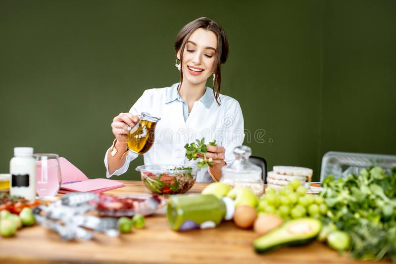 Dietitian making a salad. Woman dietitian working on a healthy diet pouring olive oil into the salad sitting at the table full of various healthy food indoors royalty free stock images