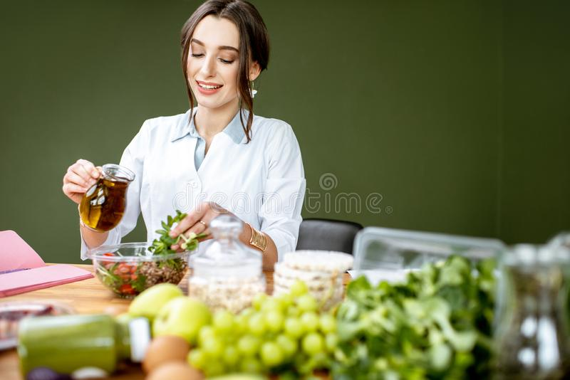 Dietitian making a salad. Woman dietitian working on a healthy diet pouring olive oil into the salad sitting at the table full of various healthy food indoors stock image