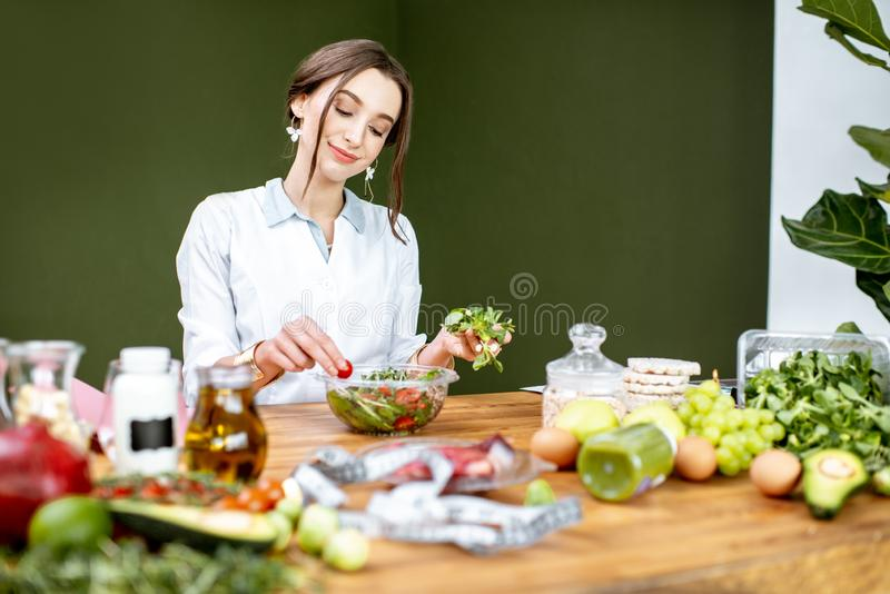 Dietitian mixing a salad. Woman dietitian working on a healthy diet making a salad with different raw products at the working place royalty free stock image