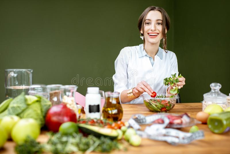 Dietitian mixing a salad. Woman dietitian working on a healthy diet making a salad with different raw products at the working place royalty free stock photography