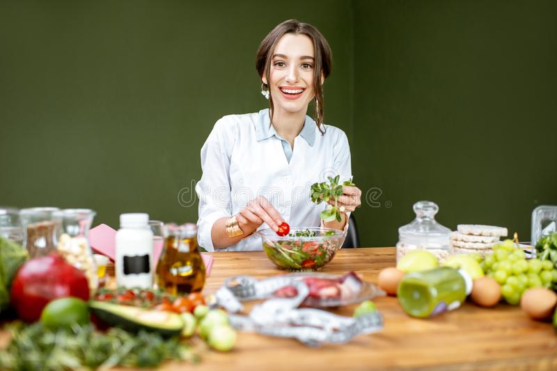 Dietitian mixing a salad. Woman dietitian working on a healthy diet making a salad with different raw products at the working place royalty free stock photo