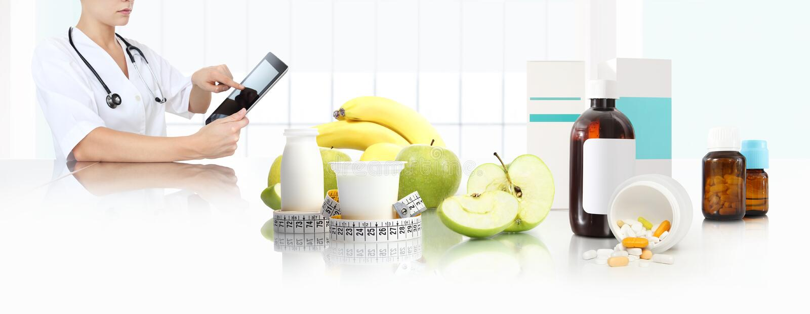 Dietitian nutritionist doctor prescribes prescription by consulting the digital tablet at the desk office with fruits and yogurt royalty free stock images