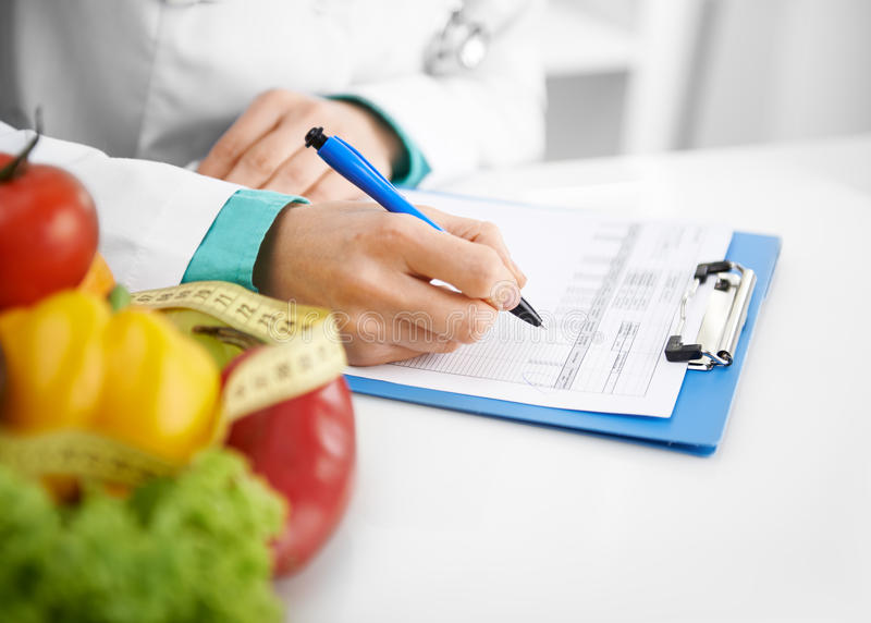 Dietitian prescribing treatment. Doctor nutritionist writing case history in the office. Young woman dietitian prescribing recipe royalty free stock images