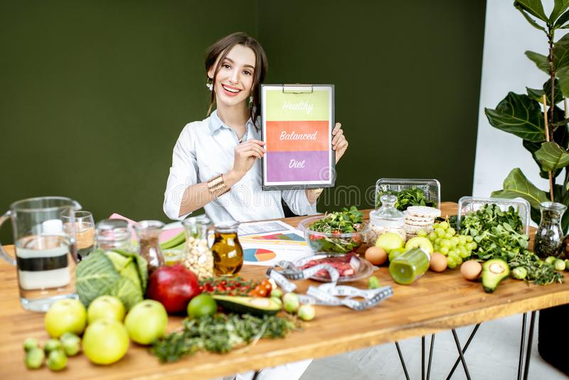 Dietitian promoting healthy balanced eating. Sitting at the table full of variuos products stock image