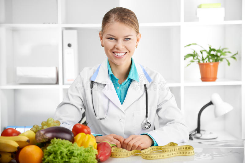 Dietitian with tape. Happy smiling female dietitian in uniform with stethoscope at workplace. Young woman doctor sitting at the desk with eco food stock photography