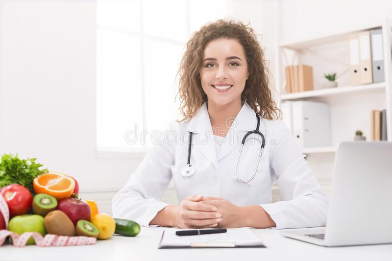 Dietitian working on diet plan at office, smiling at camera. Weight loss and right nutrition. Dietitian working on diet plan at office, smiling at camera, free royalty free stock photography