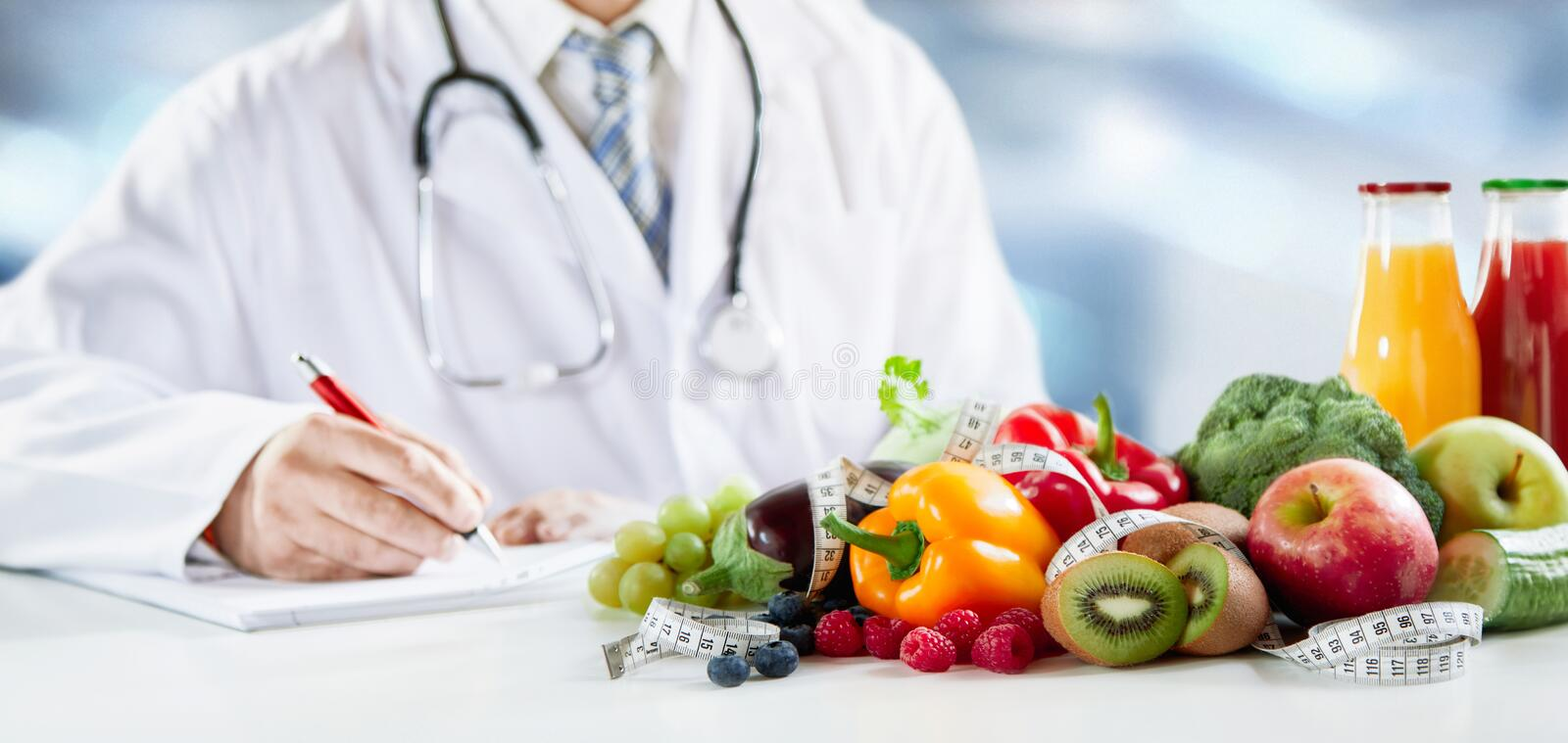 Dietitian writing a prescription for healthy diet. Dietitian writing a prescription for a healthy diet with assorted fresh fruit and vegetables in the foreground stock image