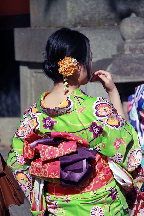 Dietro della donna in vestito verde dal kimono ed il telaio rosa-intenso in tempio giapponese fotografia stock libera da diritti