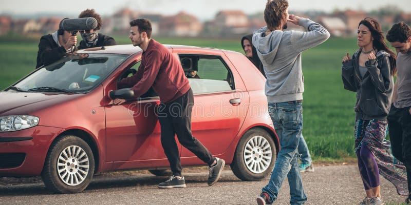 Dietro improvvisazione di scena Il gruppo delle troupe cinematografica che spinge l'automobile con è venuto fotografia stock libera da diritti