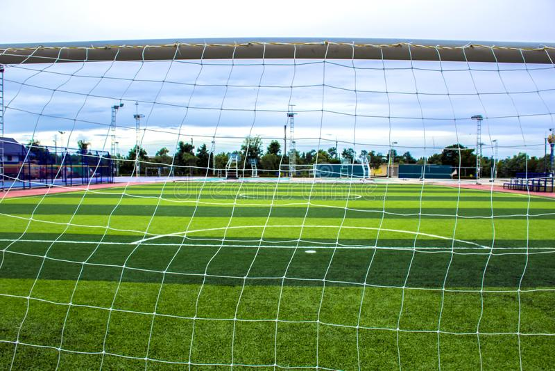 Dietro la rete del ` s del portiere Stadio dell'erba del campo di calcio e di calcio immagini stock libere da diritti
