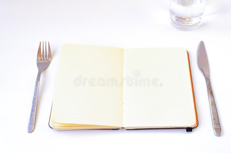 Diets concept. Open notebook on the table. With plate, cutlery and glass of water; with white background royalty free stock images
